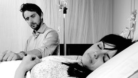 Sad husband worried for his sick wife  that is sleeping in a hospital bed black and white. Man reading while waiting in hospital next to sick woman Royalty Free Stock Image