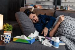 Sad ill man wanting to take his pills. Time for medicine. Sad ill man wanting to take his pills while lying on the sofa stock photography