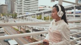 A sad Indonesian girl walks through the transition in the center of the city in white headphones and listens to music. A sad Indonesian girl walks through the stock video footage