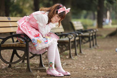 Sad japanese girl. Alone and sad japanese girl in lolita fashion sitting on bench, Tokyo stock image
