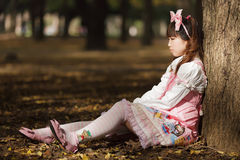 Sad japanese lolita. Leaning against tree in park royalty free stock photos