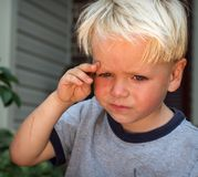 Sad kid. Little boy wiping off his tears Stock Image