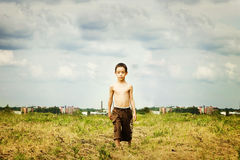 Sad kid. Is walking in the field against ugly industrial background with artistic shadows added Royalty Free Stock Photo