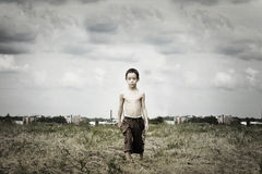 Sad kid. Is walking in the field against ugly industrial background with artistic shadows added Royalty Free Stock Image