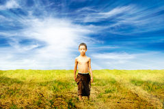 Sad kid. Is walking in the field in the sunlight Royalty Free Stock Photography
