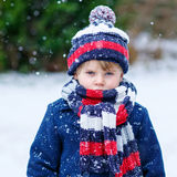 Sad kid boy in colorful winter clothes having fun with snow, out Royalty Free Stock Photography