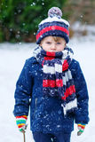 Sad kid boy in colorful winter clothes having fun with snow, out Royalty Free Stock Photo