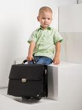 Sad kid with briefcase on stairs Stock Photography
