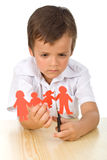 Sad kid cutting up paper people family Royalty Free Stock Image