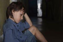Sad kid in dark room Stock Images