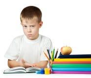 Sad kid is doing his homework Stock Photography