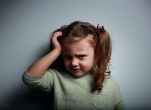 Sad kid girl with headache looking unhappy. On dark background Royalty Free Stock Photos