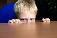 Sad kid hiding. Sad upset unhappy boy kid hiding under the table Stock Images