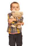 Sad kid hugging teddy. Sad kid boy hugging teddy bear and looking you isolated on white background Stock Photos