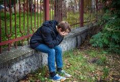 Sad Kid outdoor. Sorrowful Kid sit on the City Street Royalty Free Stock Photos