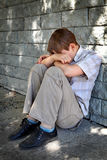 Sad Kid outdoor. Sad and Troubled Kid sit by the Wall outdoor stock photo