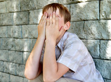 Sad Kid outdoor. Sad and Troubled Kid sitting by the Wall Stock Photography