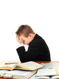 Sad Kid on the School Desk. Stressed Kid at the School Desk with a Books Isolated on the White Background Royalty Free Stock Images