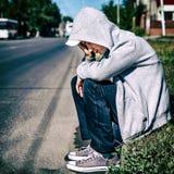Sad Kid outdoor. Sad Kid sit on the City Street Royalty Free Stock Image