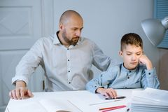 Sad kid sitting at a table next to his father, who is angry at him. Sad kid sitting at a table with books and notebooks next to his father, who is angry at him stock photo