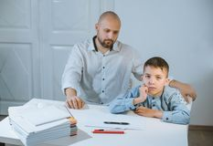 Sad kid sitting at a table next to his father, who is angry at him. Sad kid sitting at a table with books and notebooks next to his father, who is angry at him royalty free stock image