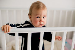 Sad kid standing in crib Royalty Free Stock Images