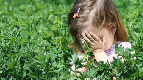 Sad kid crying in tall grass Stock Image