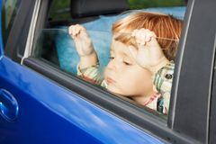 Sad kid tired of trip. Little kid is sitting sad on the back sit and look tired of car trip Stock Photography