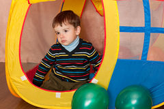 Sad kid in a toy house Stock Photography