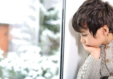 Sad kid on window cannot go out. Because of cold and snow Stock Image
