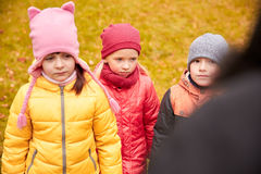 Sad kids being blamed for misbehavior outdoors. Childhood, leisure, friendship and people concept - group of sad kids being blamed for misbehavior in autumn park royalty free stock photos