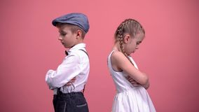 Sad kids couple standing back in silence after quarrel, isolated pink background. Stock photo royalty free stock image