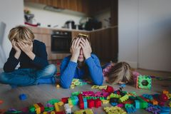 Sad kids with stressed father with toys scattered all over the room. Difficult parenting royalty free stock image