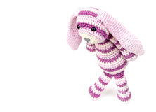 Sad knitted rabbit toy goes over white background Royalty Free Stock Images