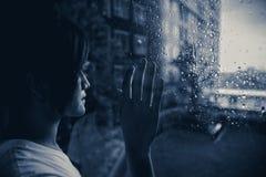 SAD kvinna som ut ser på fönster som regnar droppar arkivfoto