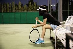 Sad lady tennis player sitting in the court after lose a match stock photo