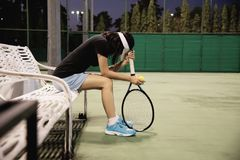Sad lady tennis player sitting in the court after lose a match stock photos