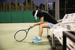 Sad lady tennis player sitting in the court after lose a match royalty free stock photo