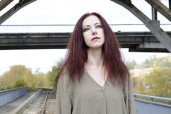 Sad lady under bridge. Sad woman in loose tunic against railroad track under a bridge Stock Photography