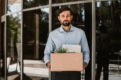 Sad laid off executive is leaving workplace with stuff. Waist up portrait of sorrowful man standing at entrance of business center. He is being dismissed from stock image