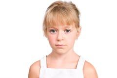 SAD liten flicka med den allvarliga framsidan på white Royaltyfri Bild
