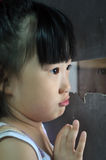 Sad little asian child looks into the window Stock Images