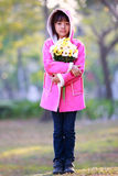 Sad little asian girl holding a bunch of flowers Stock Photo