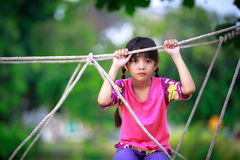 Sad little asian girl sitting alone on a playground Royalty Free Stock Images