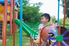 Sad little Asian kid at the playground under the sunlight in sum. Mer, Kids play on school yard. color tone, shallow DOF Stock Photo