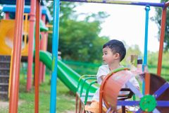 Sad little Asian kid at the playground under the sunlight in sum. Mer, Kids play on school yard. color tone, shallow DOF Royalty Free Stock Photo
