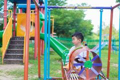 Sad little Asian kid at the playground under the sunlight in sum. Mer, Kids play on school yard. color tone, shallow DOF Stock Images