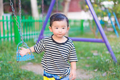 Sad little Asian kid at the playground under the sunlight in sum. Mer, Kids play on school yard. shallow DOF Stock Image