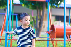 Sad little Asian kid at the playground under the sunlight in sum. Mer, Kids play on school yard. shallow DOF Stock Photo