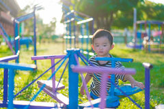 Sad little Asian kid at the playground under the sunlight in sum. Mer, Kids play on school yard. shallow DOF Stock Photos
